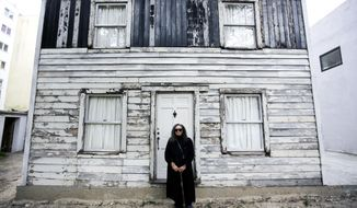 FILE - In this April 6, 2017 file photo, Rhea McCauley, a niece of the late civil rights activist Rosa Parks, poses in front of the rebuilt house of Rosa Parks in Berlin. McCauley donated the house, originally located in Detroit, to American artist Ryan Mendoza who dismantled and and rebuilt it in the German capital. Brown University said in October it is looking to temporarily relocate the house from Berlin to Providence, R.I. (AP Photo/Markus Schreiberl, File)