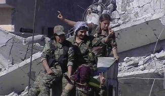 This frame grab from a video released on Thursday, Oct. 19, 2017 provided by Ronahi TV, a Kurdish TV channel media outlet that is consistent with independent AP reporting, shows members of a Kurdish female militia, the Women's Protection Units, flashing victory signs as they celebrate the victory against the Islamic State group, in Raqqa, Syria. The militia that took part in freeing the northern Syrian city of Raqqa from the Islamic State group said it will continue the fight to liberate women living under the extremist group's brutal rule. (Ronahi TV, via AP)