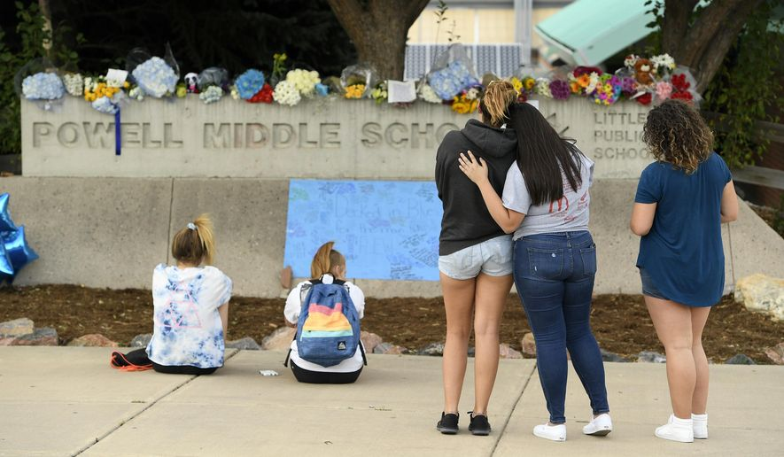 This photo taken Aug. 31, 2017, shows students pausing to reflect at a memorial at Powell Middle School set up for a student who recently took their own life in Littleton, Colo. The young student took his own life at Twain Elementary School. Two young students from Littleton Public Schools have taken their own lives over a two day period concerning parents, students and schools. (Helen H. Richardson/The Denver Post via AP)