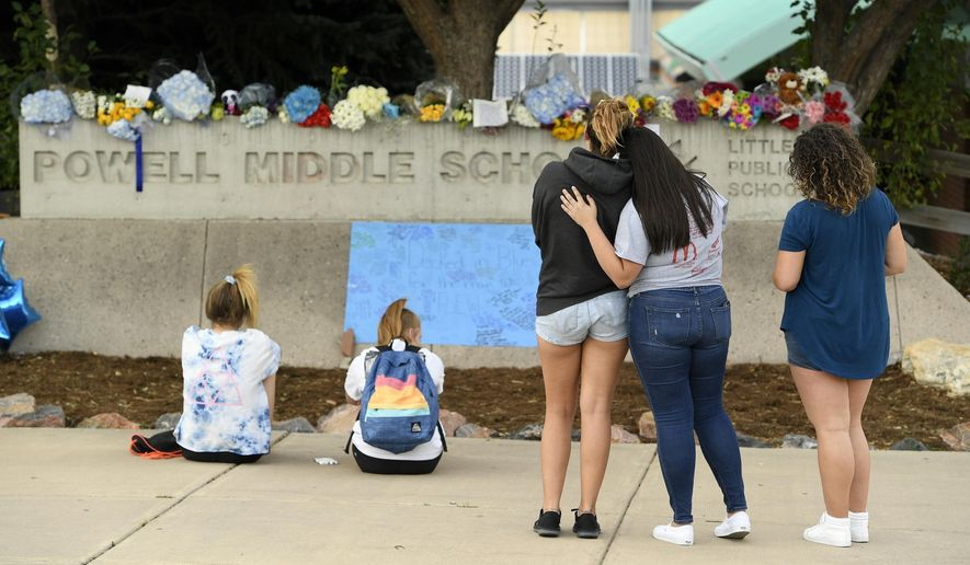 This photo taken Aug. 31, 2017, file shows students pausing to reflect at a memorial at Powell Middle School set up for a student who recently took their own life in Littleton, Colo. The young student took his own life at Twain Elementary School. Two young students from Littleton Public Schools have taken their own lives over a two-day period concerning parents, students and schools. (Helen H. Richardson/The Denver Post via AP) ** FILE **