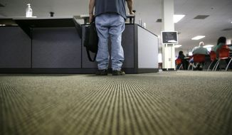 FILE - In this Friday, March 10, 2017, file photo, a lone job seeker checks in at the front desk of the Texas Workforce Solutions office in Dallas. On Thursday, Oct. 19, 2017, the Labor Department reports on the number of people who applied for unemployment benefits a week earlier. (AP Photo/LM Otero, File)