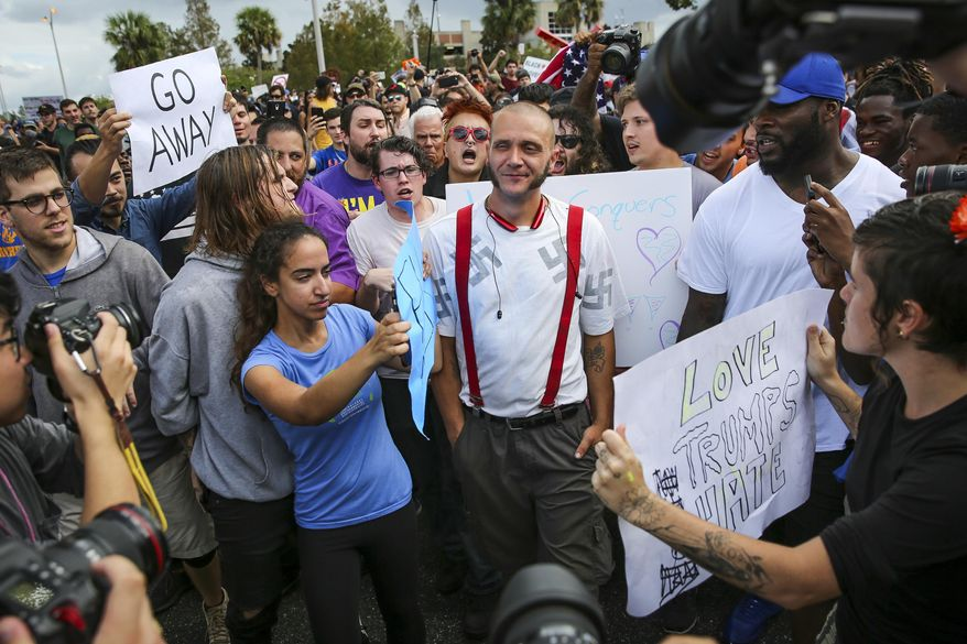 Protesters confront a man wearing a shirt with swastikas outside a University of Florida auditorium where white nationalist Richard Spencer was preparing to speak, Thursday, Oct. 19, 2017 in Gainesville, Fla. (Will Vragovic/Tampa Bay Times via AP)