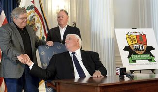 West Virginia Gov. Jim Justice, center, shakes hands with West Virginia Great Barrel Co. managing partners Tom Crabtree, left, and Philip Cornett following the announcement Thursday, Oct. 19, 2017, in Charleston W.Va., that a barrel-making facility will be constructed in White Sulphur Springs. The company that makes whiskey barrels out of white oak wood has been born from efforts to rebuild a devastated West Virginia community following deadly floods. (Chris Dorst/Charleston Gazette-Mail via AP)