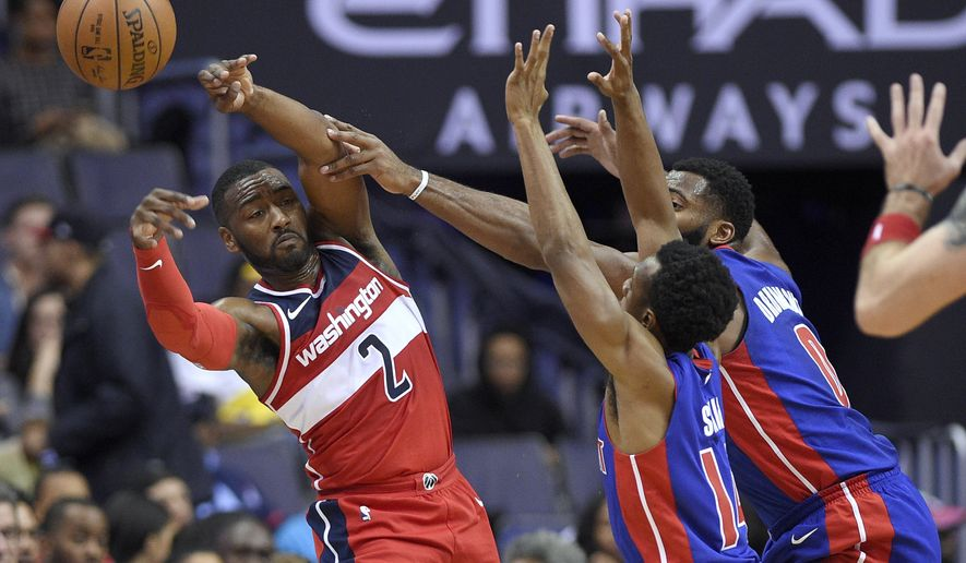 Washington Wizards guard John Wall (2) passes the ball against Detroit Pistons guard Ish Smith (14) and center Andre Drummond (0) during the first half of an NBA basketball game, Friday, Oct. 20, 2017, in Washington. (AP Photo/Nick Wass)