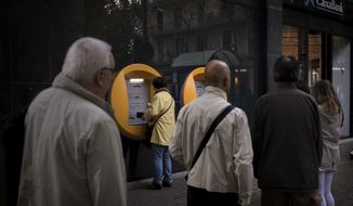 People wait to withdraw money from ATMs at a brach of CaixaBank, in Barcelona, Spain, Friday, Oct. 20, 2017. Bank customers in Catalonia are withdrawing money from financial institutions as CaixaBank and Banco Sabadell, that have moved their official headquarters to other locations in Spain amid a political crisis over the region's independence bid. (AP Photo/Emilio Morenatti)