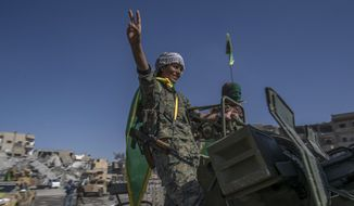 In this Thursday, Oct. 19, 2017 photo, fighters from the Women's Protection Units, or YPJ, hold a celebration in Paradise Square in Raqqa, Syria. The Kurdish female militia that took part in freeing the northern Syrian city of Raqqa from the Islamic State group said on Thursday it will continue the fight to liberate women from the extremists' brutal rule. (AP Photo/Gabriel Chaim)
