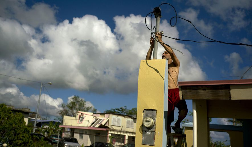 In this Friday, Oct. 13, 2017 photo, a resident tries to connect electrical lines downed by Hurricane Maria in preparation for when electricity is restored in Toa Baja, Puerto Rico. A month after the storm rolled across the center of Puerto Rico, power is still out for the vast majority. (AP Photo/Ramon Espinosa)