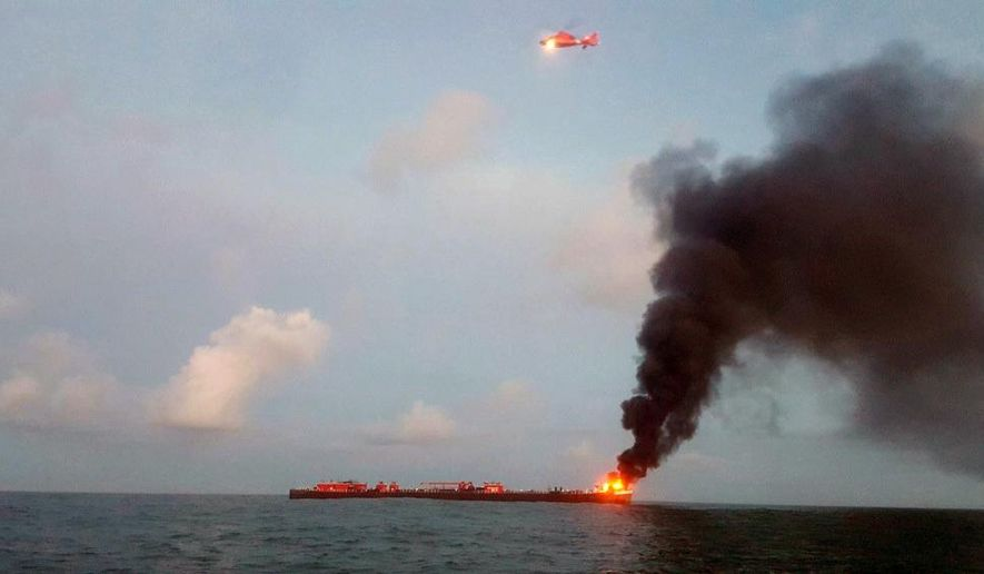 This photo provided by the U.S. Coast Guard shows a barge on fire approximately three miles from Port Aransas, Texas, jetties, Friday. Oct. 20, 2017. A Coast Guard Corpus Christi MH-65 Dolphin and HC-144 Ocean Sentry are searching for two missing crew members. (U.S. Coast Guard via AP)