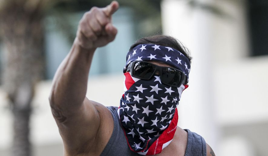 A demonstrator masked with a U.S. flag protests outside of California Republican Convention in Anaheim, Calf., on Friday, Oct. 20, 2017. Former White House adviser Steve Bannon wants to oust Republican senators he feels are disloyal to President Donald Trump. Bannon is scheduled to deliver a keynote speech at the convention, just days after leveling a blistering attack on Senate Majority Leader Mitch McConnell and other top Republicans at an Arizona fundraiser. (AP Photo/Ringo H.W. Chiu)