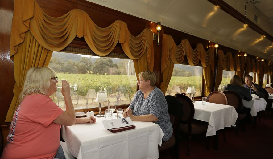 Julie Norris, left, of Florida, drinks a glass of wine while riding the Napa Valley Wine Train with Paula Anderson, of Connecticut, Thursday, Oct. 19, 2017, in Oakville, Calif. The train resumed its runs this week after last week's wildfires. The wildfires that have devastated California this month caused at least $1 billion in damage to insured property, officials said Thursday, as authorities raised the number of homes and other buildings destroyed to nearly 7,000. (AP Photo/Eric Risberg)