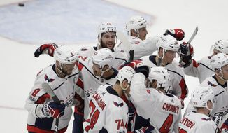Washington Capitals left wing Alex Ovechkin (8) is congratulated by teammates after scoring the winning goal in overtime of an NHL hockey game against the Detroit Red Wings, Friday, Oct. 20, 2017, in Detroit. (AP Photo/Carlos Osorio)