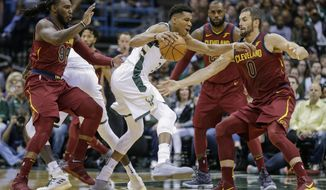 Milwaukee Bucks' Giannis Antetokounmpo tries to drive against the Cleveland Cavaliers defense during the first half of an NBA basketball game Friday, Oct. 20, 2017, in Milwaukee. (AP Photo/Tom Lynn)