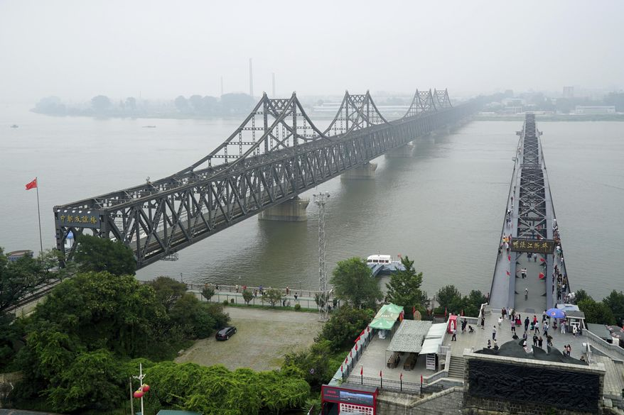 FILE - In this Sept. 9, 2017, file photo, visitors walk across the Yalu River Broken Bridge, right, next to the Friendship Bridge connecting China and North Korea in Dandong in northeastern China's Liaoning province. China and North Korea share a long border, history and ideology, but the notion that Beijing can use its influence to force Pyongyang to abandon its nuclear bombs runs against a complicated reality. Their relationship is less about friendship or political bonds than a deep and mutually uneasy dependency. (AP Photo/Emily Wang, File)