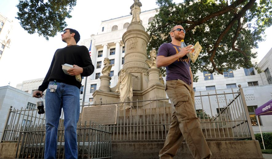 "FILE - In this Nov. 4, 2011 file photo, Sean Bordelon, left, and Raphiel Heard, of Shreveport, pause after reading the inscription on the Confederate soldier's monument in front of the Caddo Parish Courthouse in Shreveport, La. Local officials have voted to remove the Confederate monument from the courthouse grounds in the northwest Louisiana parish. The Caddo Parish Commission voted 7-5 for the measure on Thursday, Oct. 19, 2017, after hearing nearly two hours of opinions about the monument erected 111 years ago in a parish once called ""Bloody Caddo"" because so many African-Americans were killed during Reconstruction.   (Douglas Collier /The Shreveport Times via AP)"