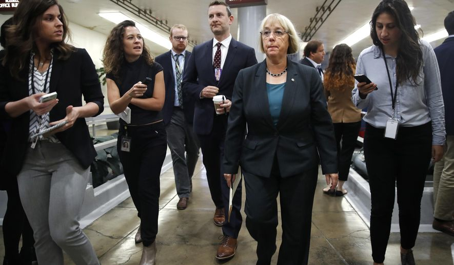 Sen. Patty Murray, D-Wash., second from right, is surrounded by reporters as she heads to vote on budget amendments, Thursday, Oct. 19, 2017, in Washington. (AP Photo/Jacquelyn Martin)
