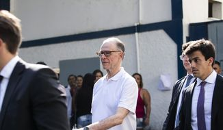 CORRECTS DAY AND DATE - Carlos Nuzman, former president of the Brazilian Olympic Committee, center, walks from a prison accompanied by his defense team, in Rio de Janeiro, Brazil, Friday, Oct. 20, 2017. Nuzman was released from Friday after his arrest two weeks ago on eventual charges that he arranged bribes to land the Olympics he headed last year in Rio. (AP Photo/Bruna Prado)