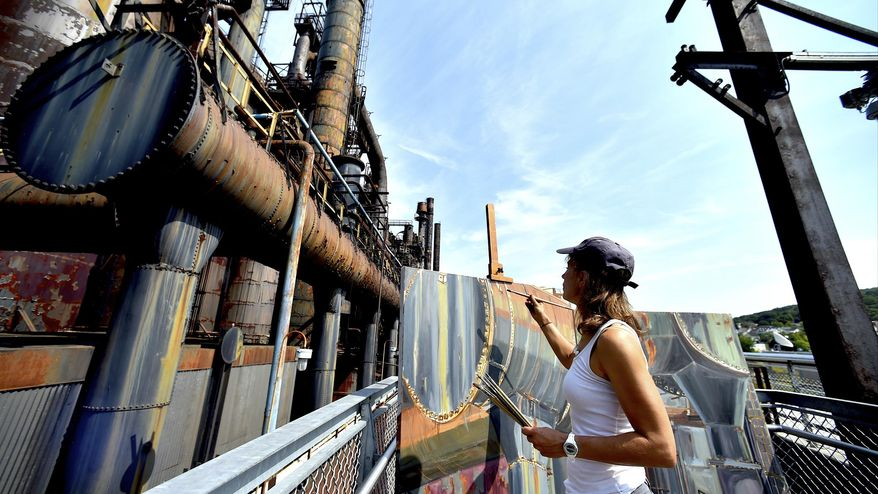In this Sept. 12, 2017 photo, artist Rachel Lussier paints the former Bethlehem Steel plant on the Hoover-Mason Trestle, in Bethlehem, Pa. Unaided by photographs or models, Lussier paints under the elements to try to grab the scope of industry. She's traveled the country, painting B29s and large battleships. Now, she pays homage to the furnaces that fueled the wars. (April Gamiz/The Morning Call via AP)