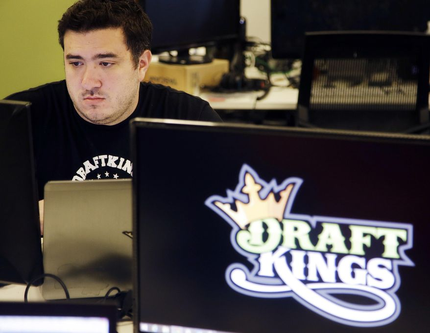 FILE - In this Sept. 9, 2015, file photo, Len Don Diego, marketing manager for content at the DraftKings daily fantasy sports company, works at his station at the company's offices in Boston. Michigan state Sen. Curtis Hertel Jr., D-East Lansing, is sponsoring legislation to regulate and make legal daily fantasy sports games popularized by sites such as FanDuel and DraftKings. (AP Photo/Stephan Savoia, File)