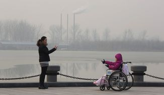 FILE - In this Dec. 12, 2015, file photo, visitors to a park gestures at each other near chimneys spewing smoke in Beijing. Environmental pollution - from filthy air to contaminated water - is killing more people every year than all war and violence in the world. One out of every six premature deaths in the world in 2015 - about 9 million - could be attributed to disease from toxic exposure, according to a major study released Thursday, Oct. 19, 2017 in The Lancet medical journal. (AP Photo/Ng Han Guan, File)