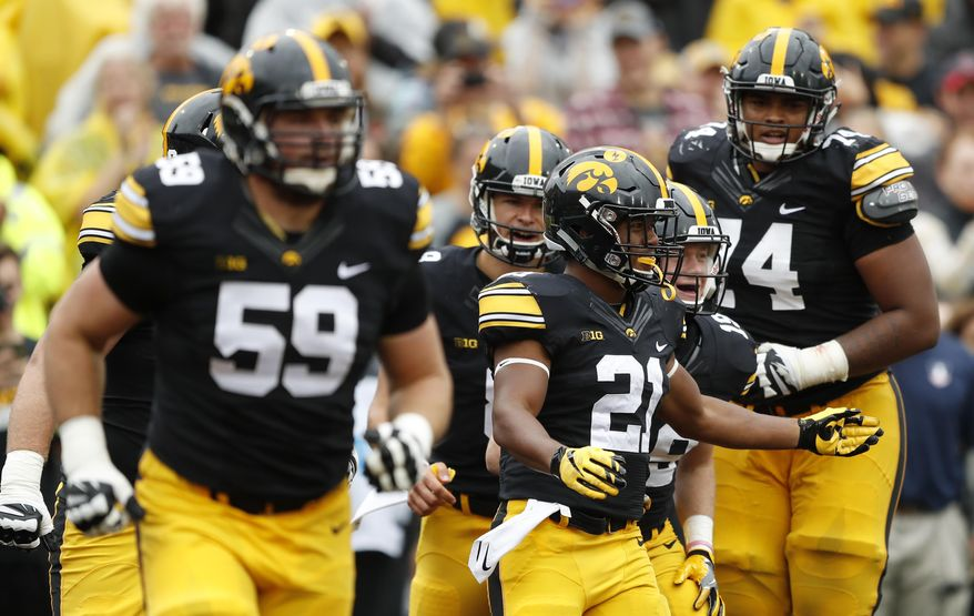 Iowa running back Ivory Kelly-Martin (21) celebrates with teammates after catching a 3-yard touchdown pass during the second half of an NCAA college football game against Illinois, Saturday, Oct. 7, 2017, in Iowa City, Iowa. Iowa won 45-16. (AP Photo/Charlie Neibergall)