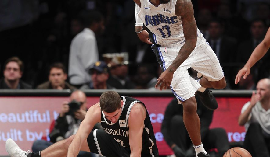 Brooklyn Nets guard Joe Harris (12) falls to the floor as he and Orlando Magic forward Jonathon Simmons (17) chase the ball during the second quarter of an NBA basketball game, Friday, Oct. 20, 2017, in New York. (AP Photo/Julie Jacobson)