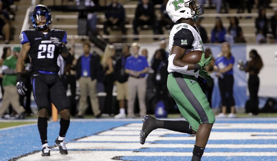 Marshall running back Keion Davis (24) scores a touchdown ahead of Middle Tennessee cornerback Darryl Randolph (29) in the first half of an NCAA college football game Friday, Oct. 20, 2017, in Murfreesboro, Tenn. (AP Photo/Mark Humphrey)