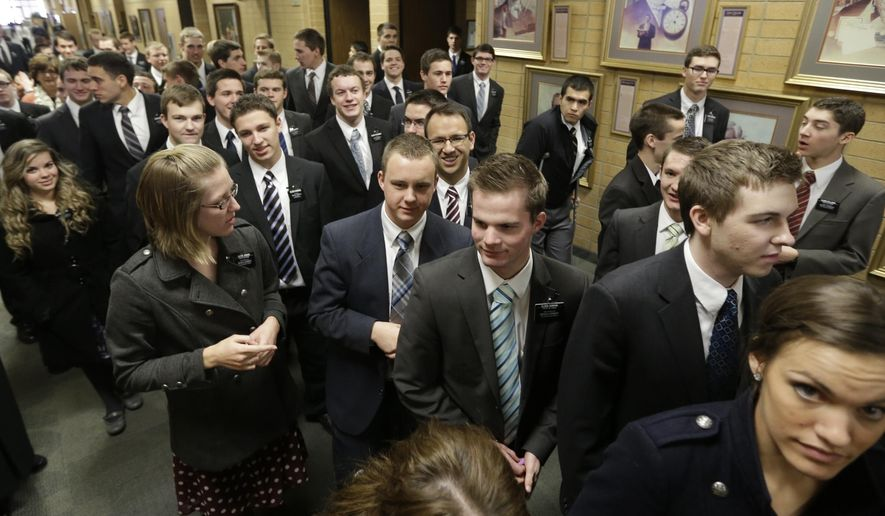 FILE - In this Jan. 8, 2013, file photo, Mormon missionaries walk through the halls at the Missionary Training Center in Provo, Utah. The Mormon church's gradual embrace of the digital age for missionaries is taking another step forward as the religion doubles the missions where technology is allowed and swaps out tablets for smartphones. (AP Photo/Rick Bowmer, File)