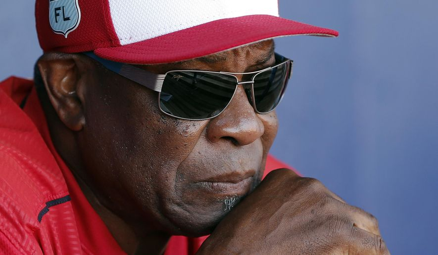 FILE - In this March 11, 2017, file photo, Washington Nationals manager Dusty Baker talks to reporters in the dugout before playing New York Mets in a spring training baseball game in Port St. Lucie, Fla. The Nationals announced Friday, Oct. 20, 2017, that Baker won't be back next season. Baker led the Nationals to the NL East title in each of his two years with the club. But Washington lost its NL Division Series both times. (AP Photo/John Bazemore, File)