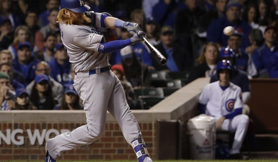 Los Angeles Dodgers' Justin Turner (10) hits an RBI single during the third inning of Game 5 of baseball's National League Championship Series against the Chicago Cubs, Thursday, Oct. 19, 2017, in Chicago. (AP Photo/Matt Slocum)