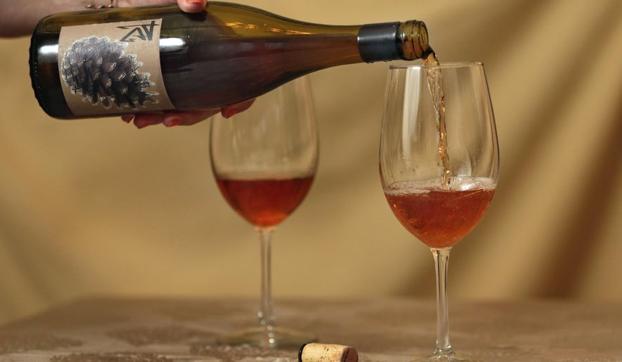 This Tuesday, Oct. 10, 2017, photo shows orange wine, a Salinia Wine Company 2012 Sonoma County Chalk Hill Pinot Gris, in New York. The unique amber-colored wine is creating a buzz in an industry long dominated by shades of red, white and rose. The orange color comes not from citrus fruit, but by fermenting white wine grapes with their skins on before pressing, a practice that mirrors the way red wines are made. (AP Photo/Richard Drew)