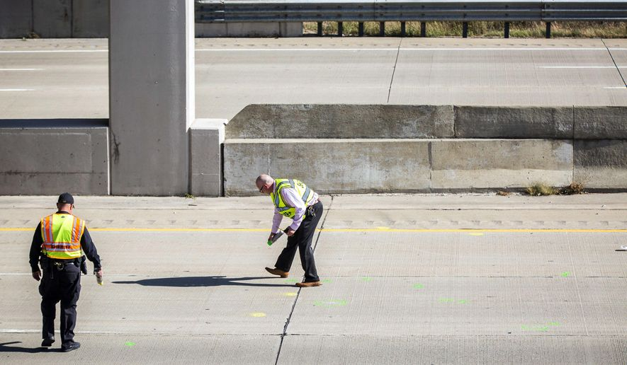 Genesee County Sheriff's officers investigate the scene of a traffic fatality Friday, Oct. 20, 2017, in Vienna Township, Mich.  where Dodge Road crosses Interstate 75. authorities are asking for the public's help in finding out who threw a rock from a highway overpass that smashed a car windshield and killed a 32-year-old man on Oct. 18.(Terray Sylvester/The Flint Journal-MLive.com via AP)