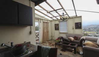 """FILE - This Sept. 21, 2017 file photo shows the damaged home of Ashley Toledo's mother in the aftermath of Hurricane Maria, in Punta Diamante, Puerto Rico. Authorities warned that people in wooden or flimsy homes should find safe shelter before Maria's expected arrival. """"You have to evacuate. Otherwise, you're going to die,"""" said Hector Pesquera, the island's public safety commissioner. """"I don't know how to make this any clearer."""" (AP Photo/Jorge A Ramirez Portela, File)"""