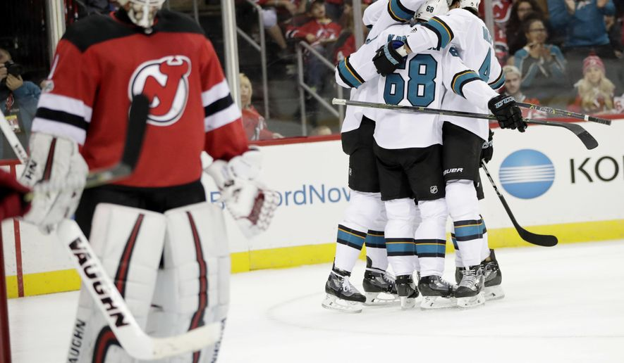 San Jose Sharks players, right, celebrate a goal by Melker Karlsson (68), of Sweden, as New Jersey Devils goalie Keith Kinkaid, left, skates away during the first period of an NHL hockey game, Friday, Oct. 20, 2017, in Newark, N.J. (AP Photo/Julio Cortez)