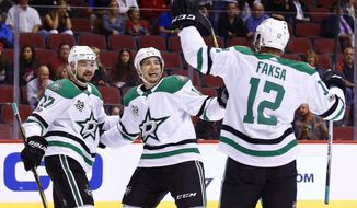 Dallas Stars center Radek Faksa (12) celebrates his goal against the Arizona Coyotes with Stars center Devin Shore (17) and Stars center Tyler Pitlick, middle, during the first period of an NHL hockey game Thursday, Oct. 19, 2017, in Glendale, Ariz. (AP Photo/Ross D. Franklin)