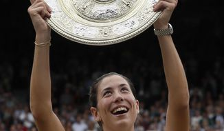 FILE - In this July 15, 2017, file photo, Spain's Garbine Muguruza holds the trophy after defeating Venus Williams of the United States in the Women's Singles final match at the Wimbledon Tennis Championships in London.  Muguruza is the WTA Player of the Year. The women's tennis tour announced the annual honors on Friday, Oct. 20, 2017. (AP Photo/Kirsty Wigglesworth, File)