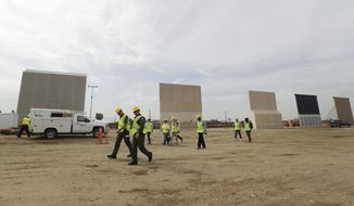 People pass border wall prototypes as they stand near the border with Tijuana, Mexico, Thursday, Oct. 19, 2017, in San Diego. Companies are nearing an Oct. 26 deadline to finish building eight prototypes of President Donald Trump's proposed border wall with Mexico. (AP Photo/Gregory Bull)