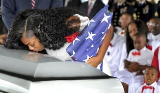 Myeshia Johnson, the wife of Army Sgt. La David Johnson, kisses her husband's casket during his funeral service at the Hollywood Memorial Gardens in Hollywood, Fla., on Saturday, Oct. 21, 2017. Sgt. Johnson was killed with three other colleagues in an ambush by extremists in Niger on Oct. 4. (Mike Stocker/South Florida Sun-Sentinel via AP)
