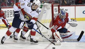 Florida Panthers center Jared McCann (90) works the puck against Washington Capitals goalie Philipp Grubauer (31), of Germany, during the first period of an NHL hockey game, Saturday, Oct. 21, 2017, in Washington. (AP Photo/Nick Wass)