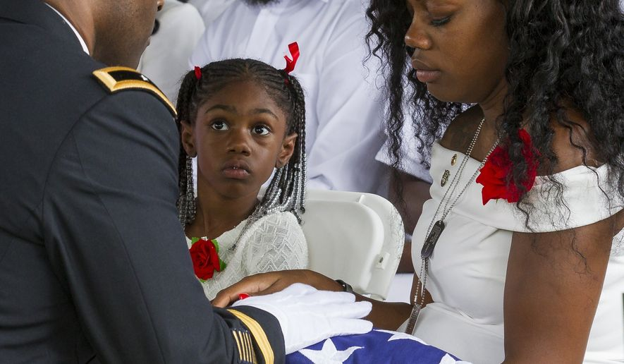 Myeshia Johnson is presented with the U.S. flag that was draped over the casket of her husband, Sgt. La David Johnson, during his burial service at Fred Hunter's Hollywood Memorial Gardens in Hollywood, Fla., on Saturday, Oct. 21, 2017. Mourners remembered not only a U.S. soldier whose combat death in Africa led to a political fight between President Donald Trump and a Florida congresswoman but his three comrades who died with him. (Matias J. Ocner/Miami Herald via AP)