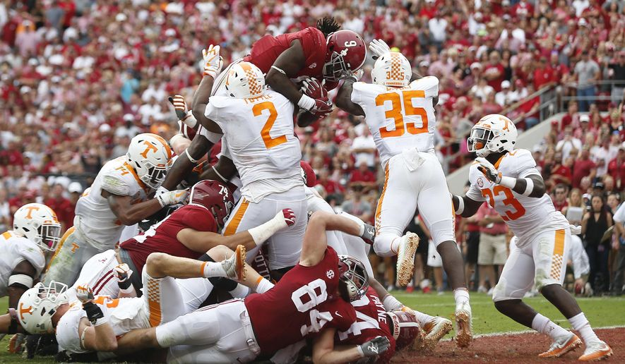 Alabama running back Bo Scarbrough leaps over Tennessee's defensive lineman Shy Tuttle, left, and linebacker Daniel Bituli, right, to score in the first half an NCAA college football game, Saturday, Oct. 21, 2017, in Tuscaloosa, Ala. (AP Photo/Brynn Anderson)