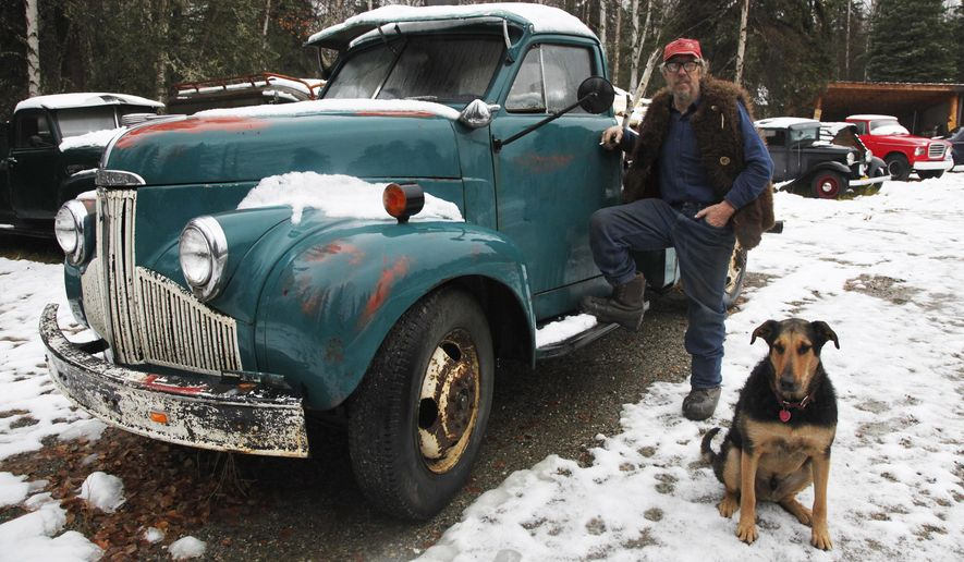 Mechanic John McDonald and his dog, Willy, pose next to McDonalds wood-hauler, a 1948 Studebaker. Oct. 10, 2017, at his home if Fairbanks, Alaska. McDonald spends much of his time buying, repairing and selling automobiles. (Robin Wood/Fairbanks Daily News-Miner via AP)