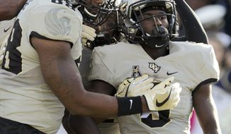 CORRECTS TO ADRIAN KILLINS NOT TRYSTEN HILL Central Florida's Adrian Killins (9) celebrates with his teammates after scoring the a touchdown during the first half of an NCAA college football game in Annapolis, Md., Saturday, Oct. 21, 2017. (AP Photo/Jose Luis Magana)