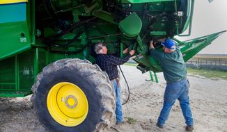 Fourth generation farmer, John Snover and his grandson, Colten Schafersman, a sixth generation farmer, repair a broken belt on a John Deere S670 Combine on their farm Wednesday, Oct 4, 2017, in Hooper, Neb. In the next 18 months or so, between 100 and 125 farmers in a rural 14-county region of eastern Nebraska will go before their local county boards, seeking permits to build chicken barns on their land.(Brendan Sullivan/The World-Herald via AP)
