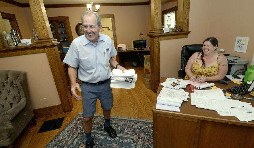 In this June 15, 2017 photos, postal carrier Larry Schultz leaves Ally Stewart laughing as he delivered mail to a law office on his route near the capitol in Lincoln, Neb.  (Eric Gregory/The Journal-Star via AP)