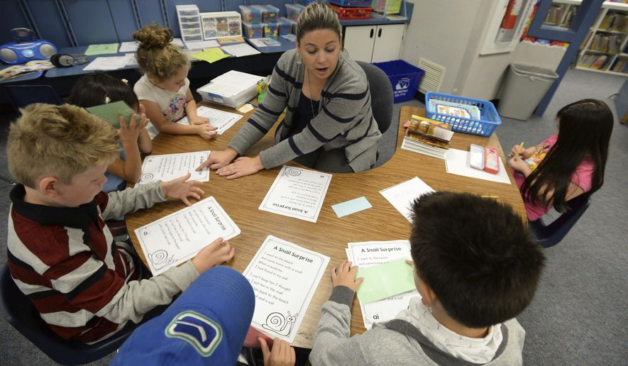 In this Sept. 28, 2017, photo, Point Roberts Elementary School teacher Jessie Hettinga works with a group of first, second and third graders on reading at the school in Point Roberts, Wa. Students are Serenity Walker, 7, from left, Fiona Laclair 7, David Dominguez, 7, Wyatt Nissen, 7, Calum Gallardo, 7, and Emme McSkimmings, 8. (Philip A. Dwyer/The Bellingham Herald via AP)