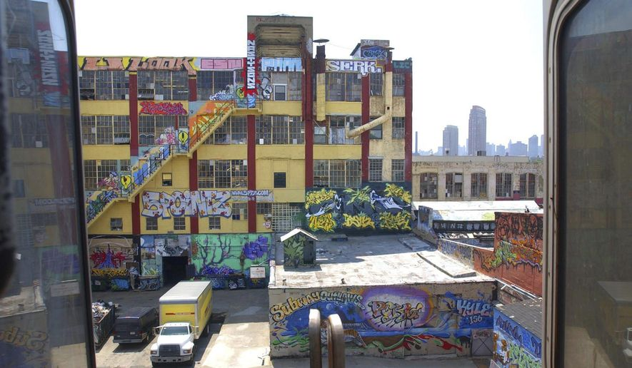 "In this July 8, 2004 file photo, a warehouse building known as ""5 Pointz"" is shown with graffiti work from various artists from around the world, is visible between cars of an elevated subway train in the Queens, N.Y. Four years after the graffiti-covered warehouse was whitewashed, a jury will decide whether the street art deserved protection under the law. (AP Photo/Frank Franklin, File)"