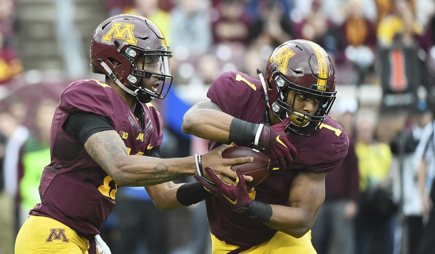 Minnesota quarterback Demry Croft fakes a handoff to running back Rodney Smith against Illinois the first half of an NCAA college football game, Saturday, Oct. 21, 2017, in Minneapolis. (AP Photo/John Autey)