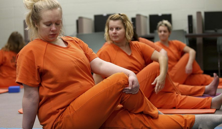 Scott County inmate Melinda Heyvaert and other inmates get into a position during a yoga class held at the Scott County Jail in Davenport, Iowa, on Wednesday, Oct. 11, 2017. The class is taught by volunteer Joan Marttila. (John Schultz/Quad City Times via AP)