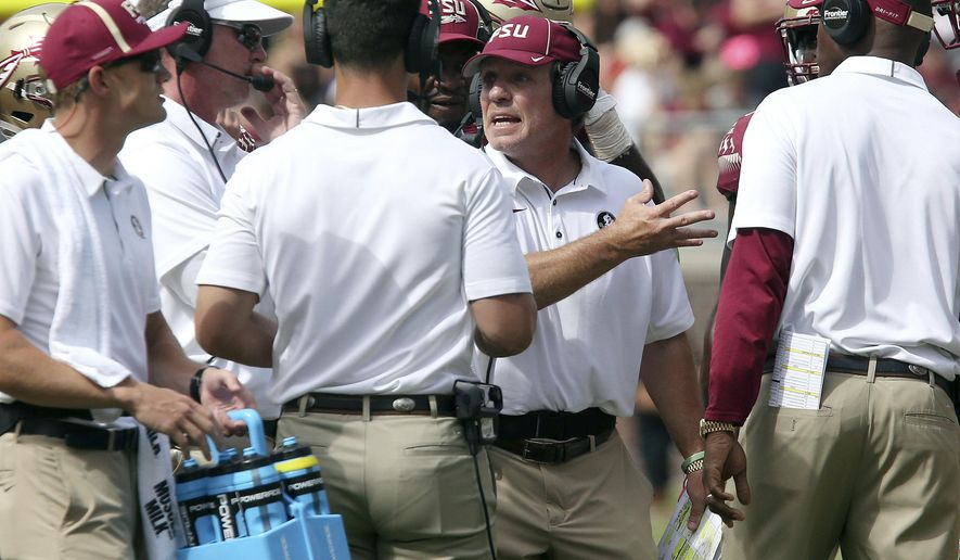 Florida State's head coach Jimbo Fisher, second from right, talks to his staff on the sideline in the fourth quarter of an NCAA college football game against Louisville, Saturday, Oct. 21, 2017, in Tallahassee Fla. Louisville won 31-28. (AP Photo/Steve Cannon)