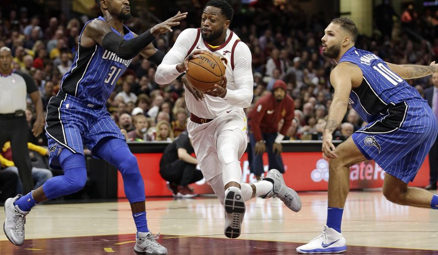 Cleveland Cavaliers' Dwyane Wade, center, drives to the basket between Orlando Magic's Terrence Ross, left, and Evan Fournier, from France, in the first half of an NBA basketball game, Saturday, Oct. 21, 2017, in Cleveland. (AP Photo/Tony Dejak)